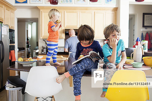 Boys eating apples at kitchen counter while father working in kitchen