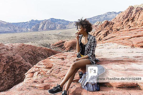 Frau schaut weg  während sie an einem sonnigen Tag Essen auf einer Felsformation isst