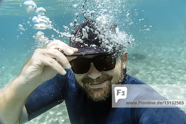 Portrait of happy man wearing sunglasses while swimming undersea