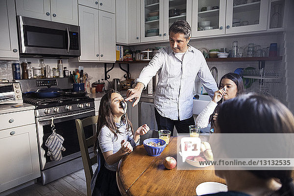 Playful girls with parents at table in kitchen