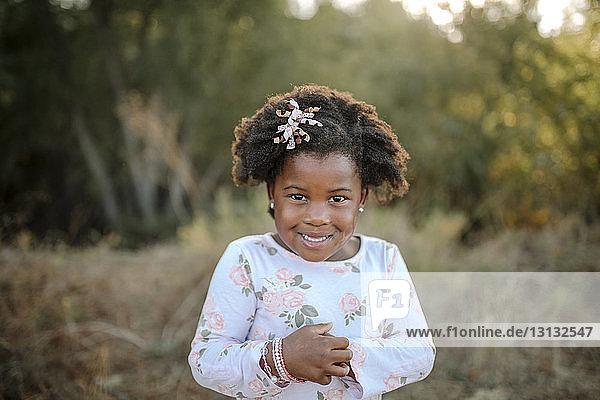 Bildnis eines lächelnden Mädchens mit lockigem Haar im Wald stehend