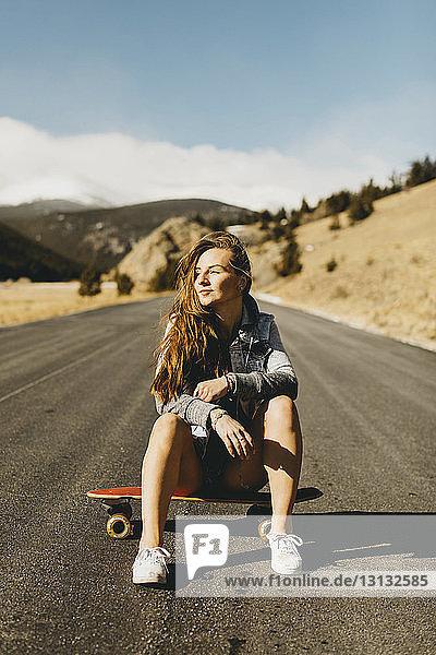 Unbeschwerte junge Frau sitzt bei Sonnenschein in voller Länge auf einem Skateboard