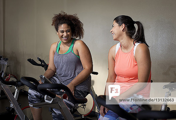 Happy female friends talking while sitting on exercise bikes in gym