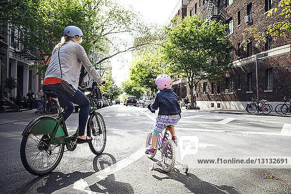 Rückansicht von Mutter und Tochter beim Fahrradfahren auf der Straße