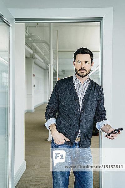 Porträt eines Geschäftsmannes  der ein Telefon hält  während er im Büro an der Tür steht