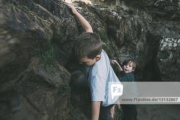 Brüder klettern an Felsformationen am Strand