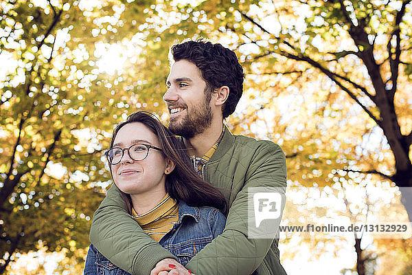 Nachdenkliches junges Paar umarmt sich im Herbst im Park