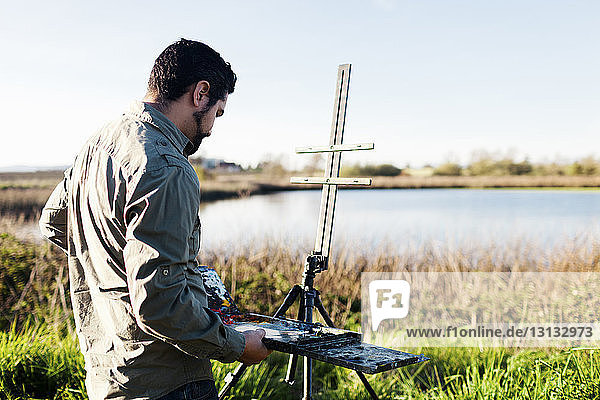 Side view of painter adjusting paint tray on easel at field