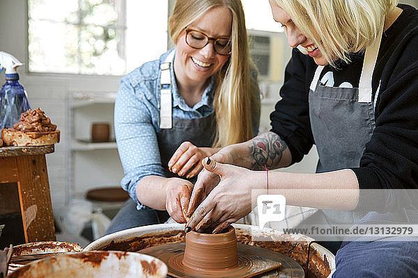 Happy women working on pottery wheel in workshop
