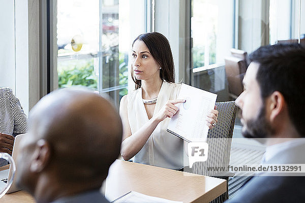 Businesswomen showing pie chart to colleagues in meeting