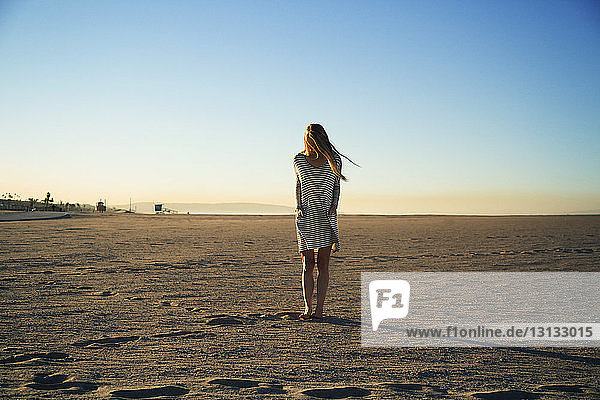 Sorglose Frau steht bei Sonnenuntergang am Strand vor strahlend blauem Himmel