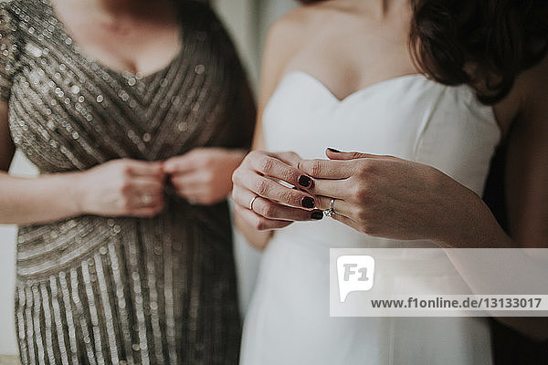 Midsection of bride wearing wedding dress while standing by bridesmaid