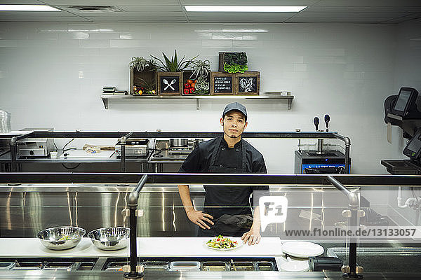 Portrait of chef standing in commercial kitchen