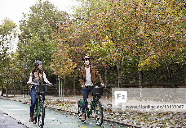 Happy couple riding bicycle on road at park