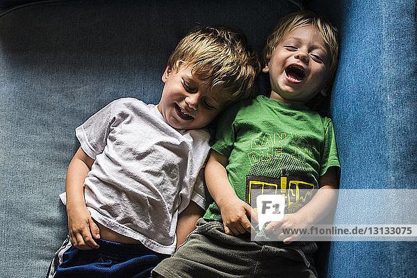 Schrägansicht von glücklichen Brüdern  die zu Hause auf dem Sofa liegen