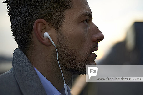 Close-up of businessman looking away while listening music
