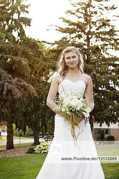 Porträt einer Braut  die einen Brautstrauss hält  während sie auf einem Grasfeld steht