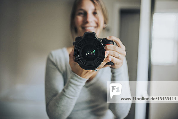 Portrait of woman holding camera while standing at home