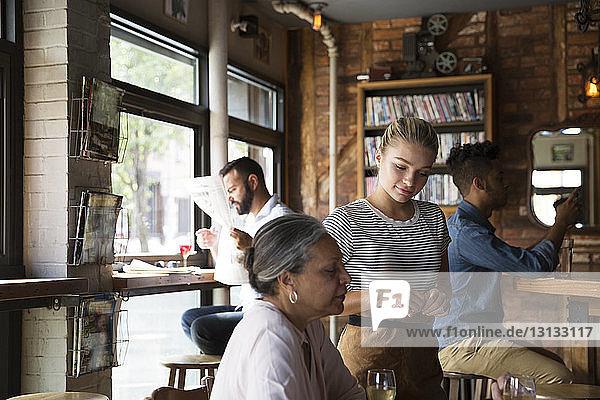 Weibliche Kellnerin steht Kunden im Café zur Seite