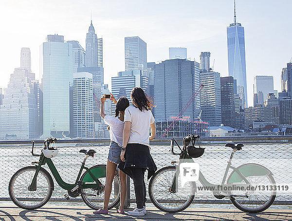 Rückansicht eines Paares  das die Stadtlandschaft am Fluss fotografiert