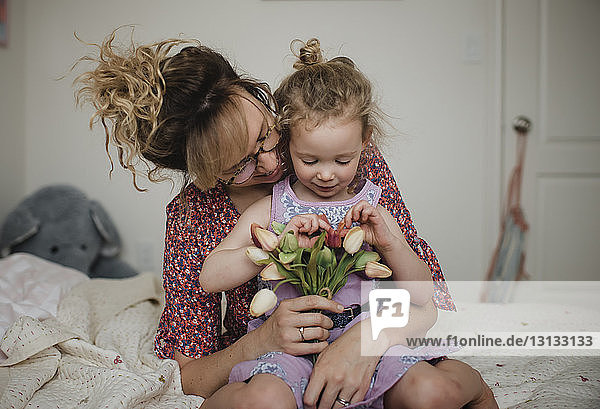 Mother with daughter holding tulips while sitting on bed at home