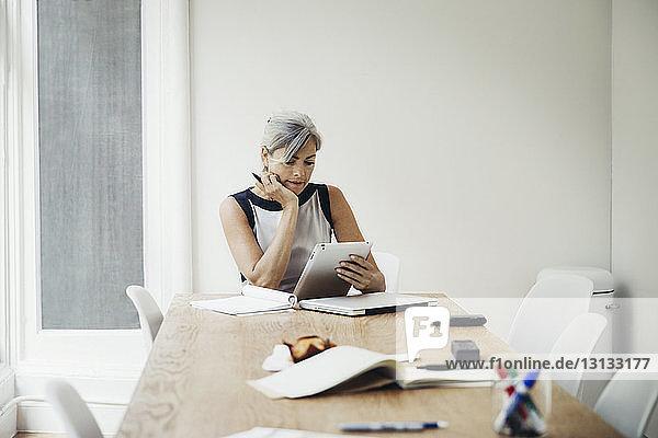 Geschäftsfrau benutzt Tablet-Computer im Sitzungssaal