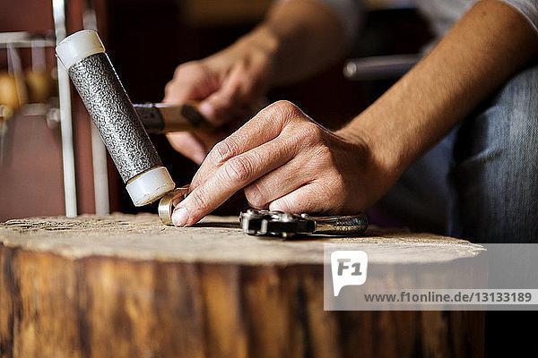 Mittelteil einer Frau  die in einem Workshop mit einem Gummihammer arbeitet Mittelteil einer Frau, die in einem Workshop mit einem Gummihammer arbeitet