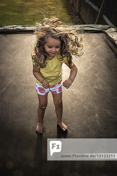 High angle view of playful girl standing on trampoline