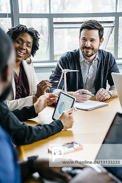 Lächelnde Geschäftsleute am Schreibtisch während einer Besprechung im Büro