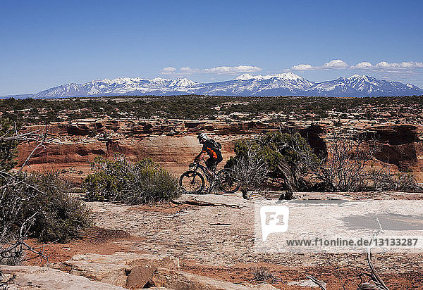 Side view of man cycling on rocks against sky