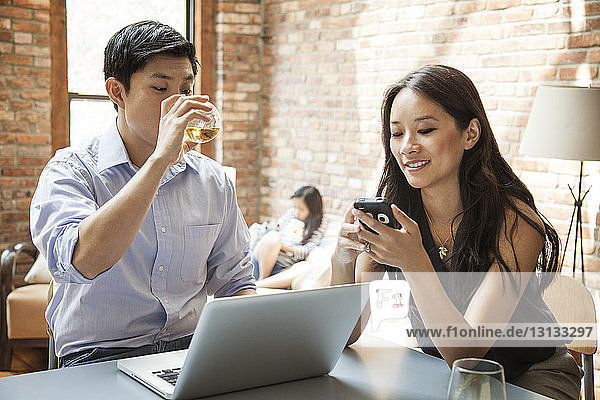 Woman using smart phone while sitting with husband at table