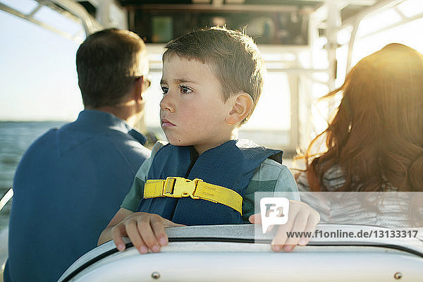 Boy looking away while traveling with parents in boat