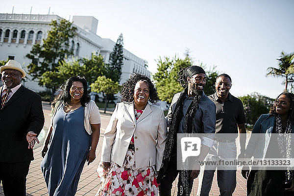 Glückliche Familie geht auf Fußweg gegen klaren Himmel