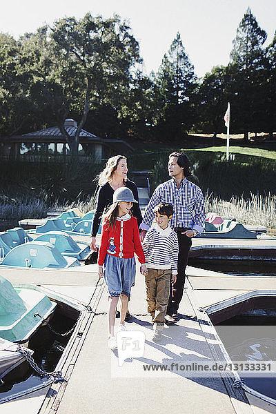 Glückliche Familie in voller Länge beim Spaziergang auf dem Pier über den See im Park bei Sonnenschein
