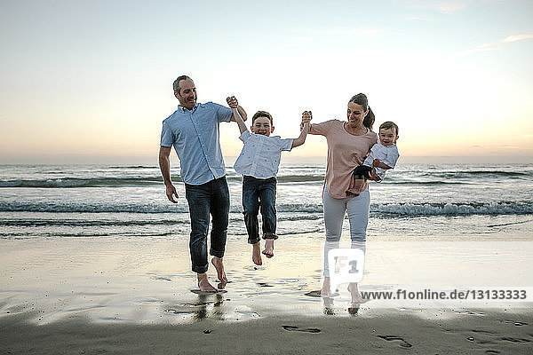 Eltern spielen mit ihrem Sohn bei Sonnenuntergang am Strand gegen den Himmel