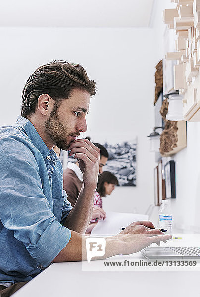 Side view of business people working at desk in office
