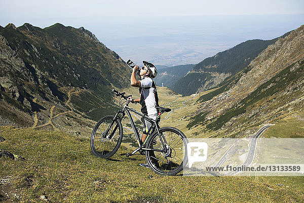 Side view of athlete drinking water while standing by bicycle on mountain