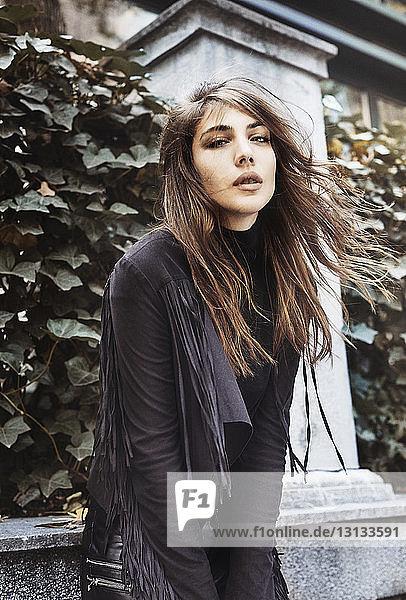 Porträt einer jungen Frau  die im Park vor Pflanzen steht