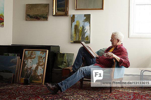 Mann betrachtet Gemälde  während er auf einem Sessel sitzt