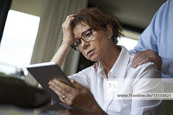 Woman using tablet computer while husband standing in background