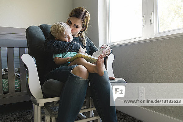 Mother kissing son while reading book on chair at home