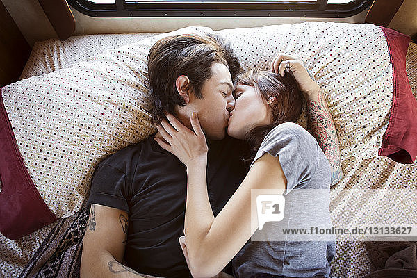Couple kissing while lying on bed in camper van