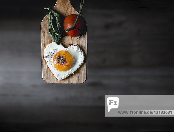 Heart shaped sunny side up egg and tomato on cutting board