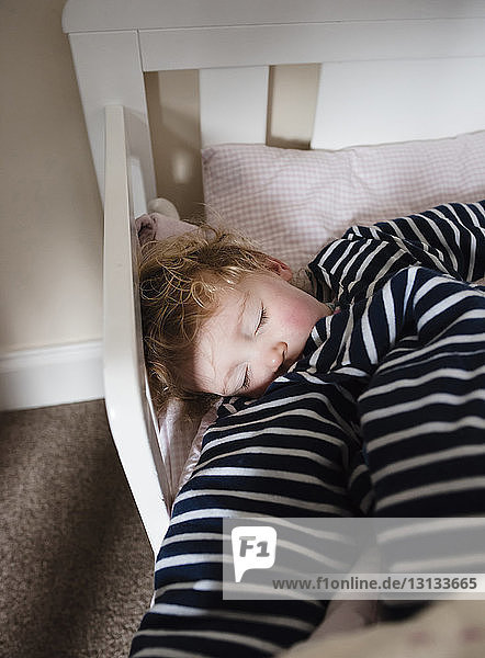 High angle view of girl sleeping in bed at home