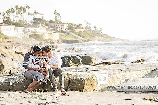 Eltern küssen ihre Tochter  während sie am Strand vor klarem Himmel sitzen