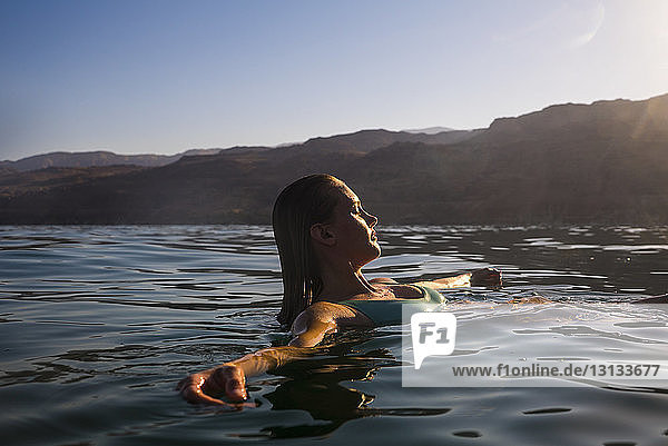 Frau schwimmt bei Sonnenuntergang im Meer gegen klaren Himmel