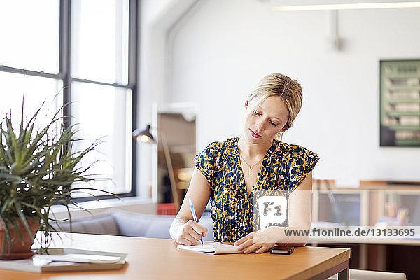 Geschäftsfrau schreibt auf Notizblock,  während sie im Büro am Tisch sitzt