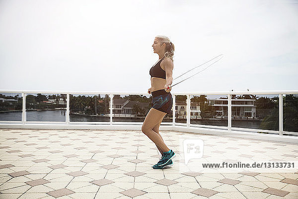 Side view of mature woman exercising with jumping rope on footpath against sky