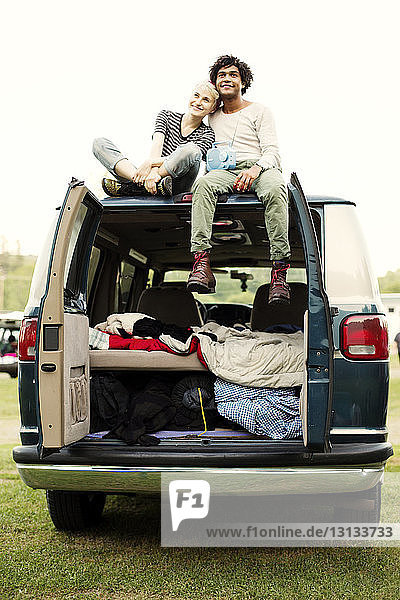 Smiling couple sitting on hood of camping van against clear sky