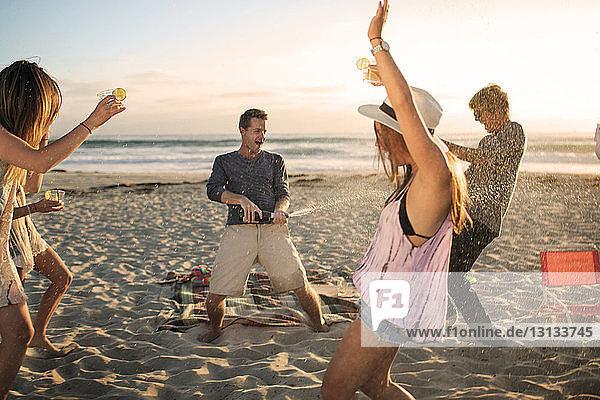 Glücklicher Mann öffnet Weinflasche  während Freunde am Strand tanzen